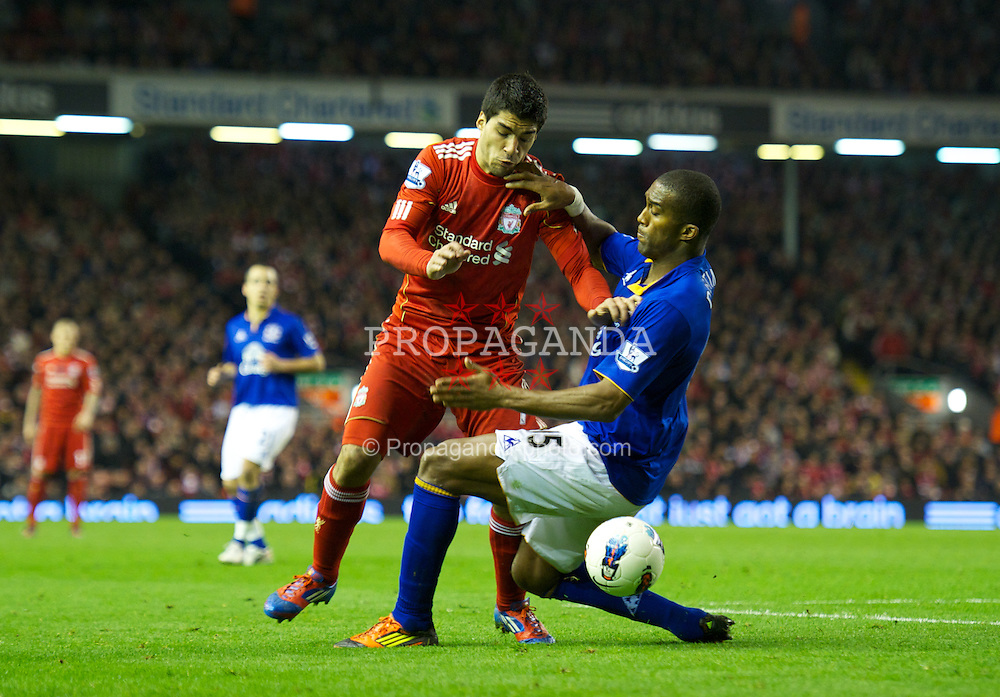 LIVERPOOL, ENGLAND - Tuesday, March 13, 2012: Liverpool's Luis Alberto Suarez Diaz in action against Everton's Sylvain Distin during the Premiership match at Anfield. (Pic by David Rawcliffe/Propaganda)