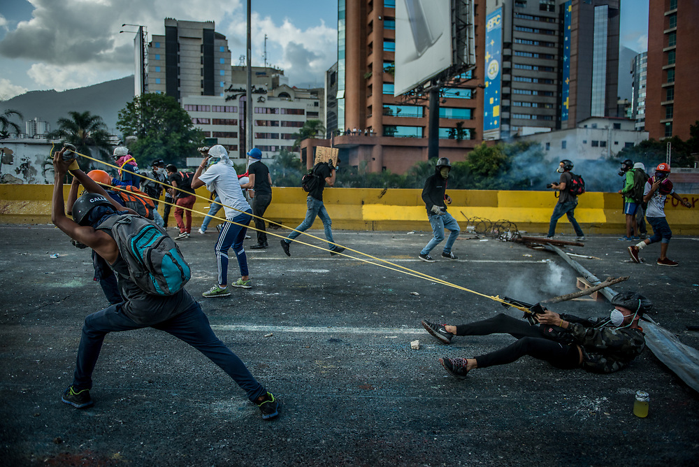 CARACAS, VENEZUELA - MAY 26, 2017:  Anti-government protesters use a giant slingshot to launch glass jars full of paint, and jars full of feces at National Guard soldiers who responded by heavily tear gassing and firing rubber bullets and buckshot at them, while fighting for control of the main highway that runs through Caracas. The streets of Caracas and other cities across Venezuela have been filled with tens of thousands of demonstrators for nearly 100 days of massive protests, held since April 1st. Protesters are enraged at the government for becoming an increasingly repressive, authoritarian regime that has delayed elections, used armed government loyalist to threaten dissidents, called for the Constitution to be re-written to favor them, jailed and tortured protesters and members of the political opposition, and whose corruption and failed economic policy has caused the current economic crisis that has led to widespread food and medicine shortages across the country.  Independent local media report nearly 100 people have been killed during protests and protest-related riots and looting.  The government currently only officially reports 75 deaths.  Over 2,000 people have been injured, and over 3,000 protesters have been detained by authorities.  PHOTO: Meridith Kohut