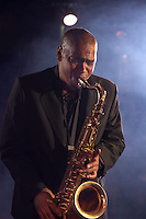 Jazz musician playing saxophone on smokey nightclub stage