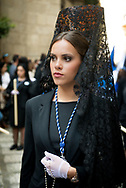 "A woman walks in formal black attire and a lace ""mantilla"" in a procession during the Holy Week in Granada, Andalusia. Spain"