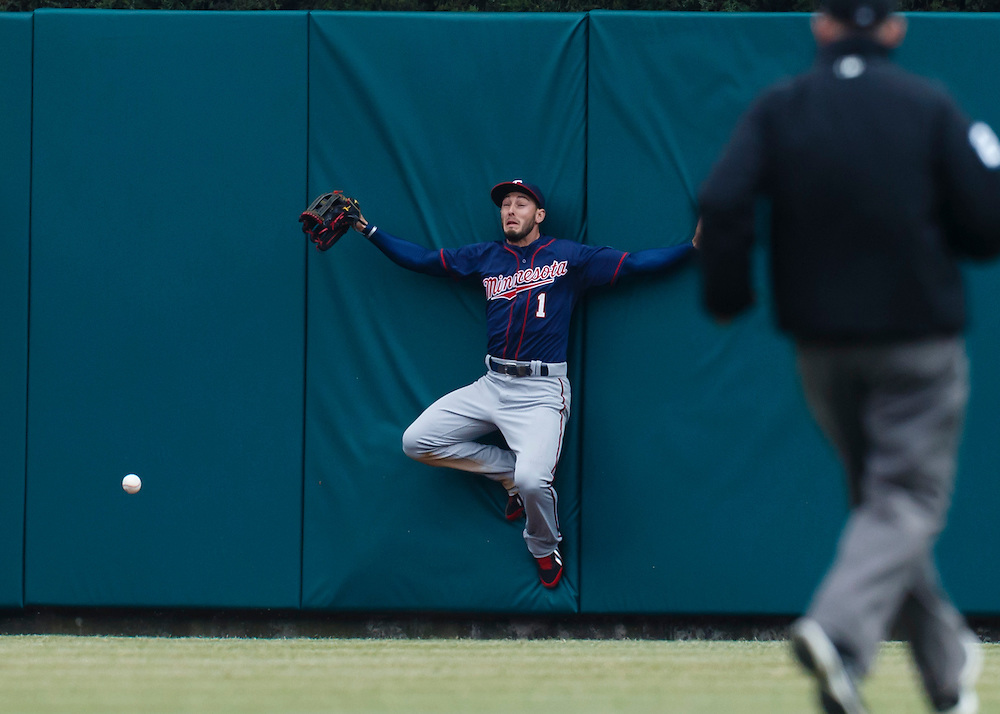 Apr 6, 2015; Detroit, MI, USA; Minnesota Twins center fielder Jordan Schafer (1) leaps onto the center field wall in an attempt to catch a ball hit by Detroit Tigers left fielder Yoenis Cespedes (not pictured) for a triple in the sixth inning at Comerica Park. Mandatory Credit: Rick Osentoski-USA TODAY Sports