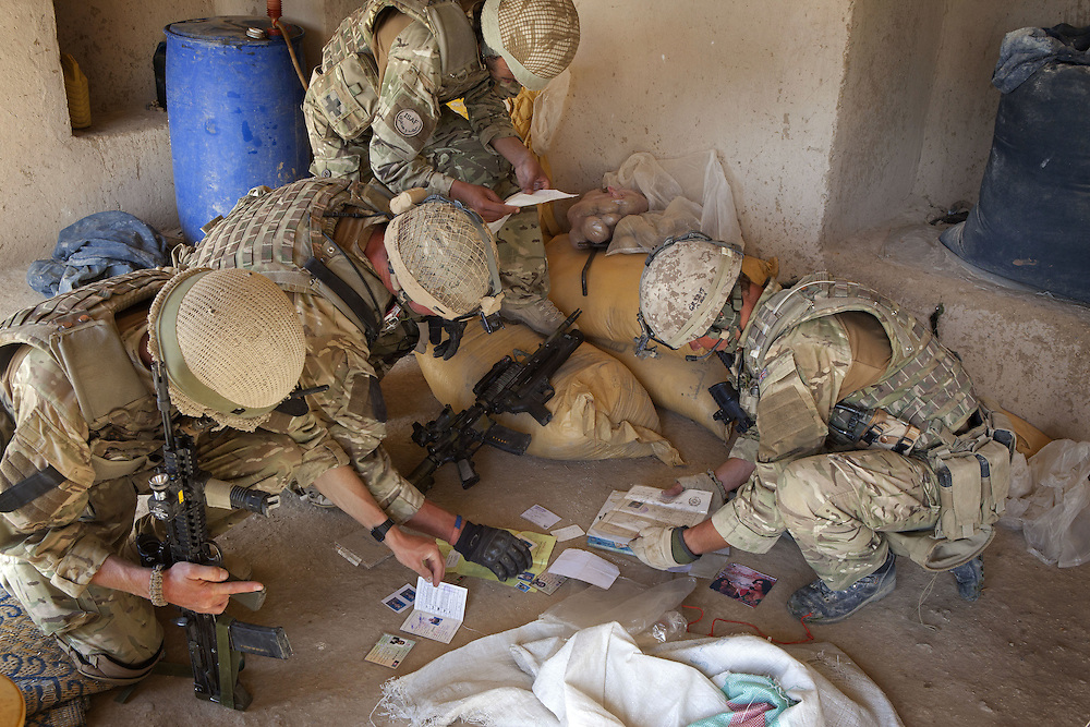 British soldiers of 16 Air Assault Bde's elite BRF (Brigade Reconnaissance Force) examines paperwork and photographs found whilst searching a compound as part of an operation in the village of Kakaran in Helmand Province, Southern Afghanistan on the 14th of March 2011.