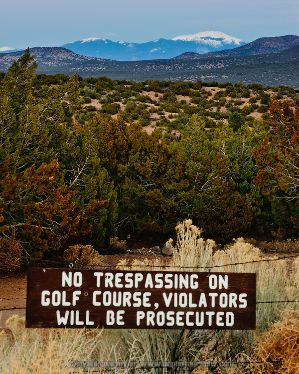 "A ""No Trespassing"" sign is posted on the fence of a golf course that appears to be wilderness near Cochiti Lake, New Mexico."