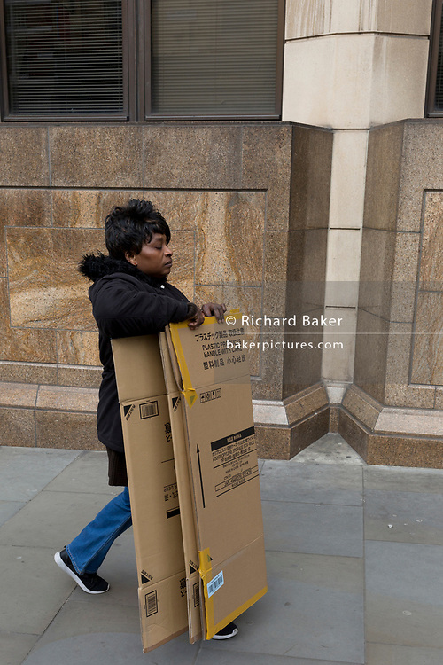 A woman carries flattened cardboard on a central London street, on 6th April 2018, in London, England.