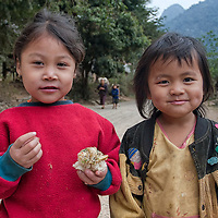 Two girls, one of them is eating sticky rice, posing for the camera in Nong Kiau.