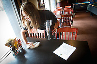 Brittiany Hart clears a table at the Coeur d'Alene Brewing Company during her shift Friday. Hart underwent nearly $30,000 of medical care after a run-in with a bobby pin in April that caused an infection which prompted an emergency surgery to save her arm and required intravenous antibiotics.