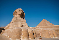 The Sphinx and a pyramid against the deep blue Egyptian sky.  At Giza, Egypt.