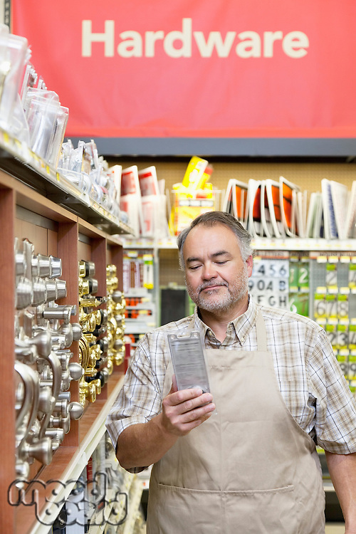 Mature salesperson reading something in hardware store