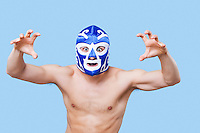 Portrait of shirtless man in wrestling mask gesturing over gray background