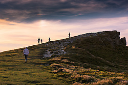 As the sun sets holidaymakers enjoy a late evning walk on the summit of Porth Island in newquay, Cornwall.