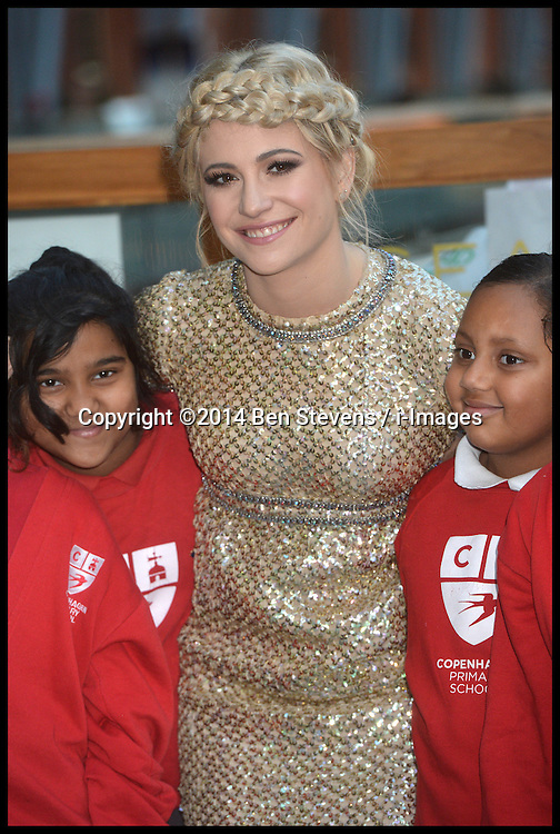 Image &copy;Licensed to i-Images Picture Agency. 16/12/2014. London, United Kingdom. <br /> <br /> Pixie Lott busks at St Pancras Station, London,  in support of Penny for London charitable revolution with children from Copenhagen Primary School.<br /> <br /> Picture by Ben Stevens / i-Images