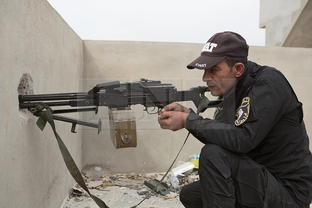 Licensed to London News Pictures. 10/11/2016. Mosul, Iraq. An Iraqi SWAT Police officer aims his PKM machine gun towards Islamic State held Mosul, some 700 metres away, from a position in the cities Gogjali District.<br /> <br /> The battle to retake Mosul, which fell June 2014, started on the 16th of October 2016 with Iraqi Security Forces eventually reaching the city on the 1st of November. Since then elements of the Iraq Army and Police have succeeded in pushing into the city and retaking several neighbourhoods allowing civilians living there to be evacuated - though many more remain trapped within Mosul. Photo credit: Matt Cetti-Roberts/LNP