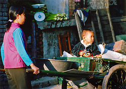China, Taiyuan, 2007. After school is time to stay with mother at the local market. Vegetable sellers in Taiyuan are open early and stay late..