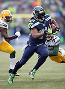 Seattle Seahawks running back Marshawn Lynch (24) runs away from would be tacklers for a 24 yard touchdown that, combined with a two point conversion, gives the Seahawks a 22-19 lead, their first of the day, during the NFL week 20 NFC Championship football game against the Green Bay Packers on Sunday, Jan. 18, 2015 in Seattle. The Seahawks won the game 28-22 in overtime. ©Paul Anthony Spinelli