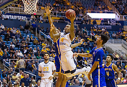 Dec 17, 2016; Morgantown, WV, USA; West Virginia Mountaineers guard Daxter Miles Jr. (4) drives down the lane and shoots during the second half against the UMKC Kangaroos at WVU Coliseum. Mandatory Credit: Ben Queen-USA TODAY Sports