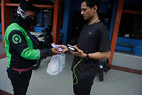 Medan, Indonesia, April 2, 2020: The daily life of a resident which stay at home seen received the delivery food packaging through an online system to avoid the spread of Corona Virus Disease-19 in Medan, North Sumatra province, Indonesia on April 2, 2020.