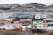 "The Melanson house, center, with white door and TV dish, in Iqaluit, Nunavut, Canada. Iqaluit, with population of 6,000, is the largest community in Nunavut as well as the capital city. It is located in the southeast part of Baffin Island. Formerly known as Frobisher Bay, it is at the mouth of the bay of that name, overlooking Koojesse Inlet. ""Iqaluit"" means 'place of many fish'. The image is part of a collection of images and documentation for Hungry Planet 2, a continuation of work done after publication of the book project Hungry Planet: What the World Eats, by Peter Menzel & Faith D'Aluisio."