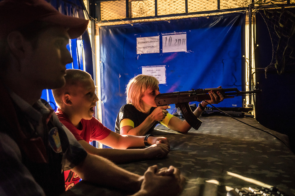 MARIUPOL, UKRAINE - AUGUST 30, 2015: A woman plays a shooting game at the Mariupol Extreme Park, an amusement park in Mariupol, Ukraine. Despite the front line being a relatively short distance away, Mariupol was lively on a warm summer weekend, with little evidence that people expect the fighting to advance this far. CREDIT: Brendan Hoffman for The New York Times