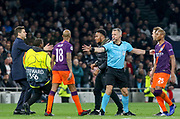Tottenham Hotspur Manager Mauricio Pochettino appeals to a pitch invader who approaches Manchester City midfielder Fabian Delph (18) during the Champions League Quarter-Final 1st leg between Tottenham Hotspur and Manchester City at Tottenham Hotspur Stadium, London, United Kingdom on 9 April 2019.