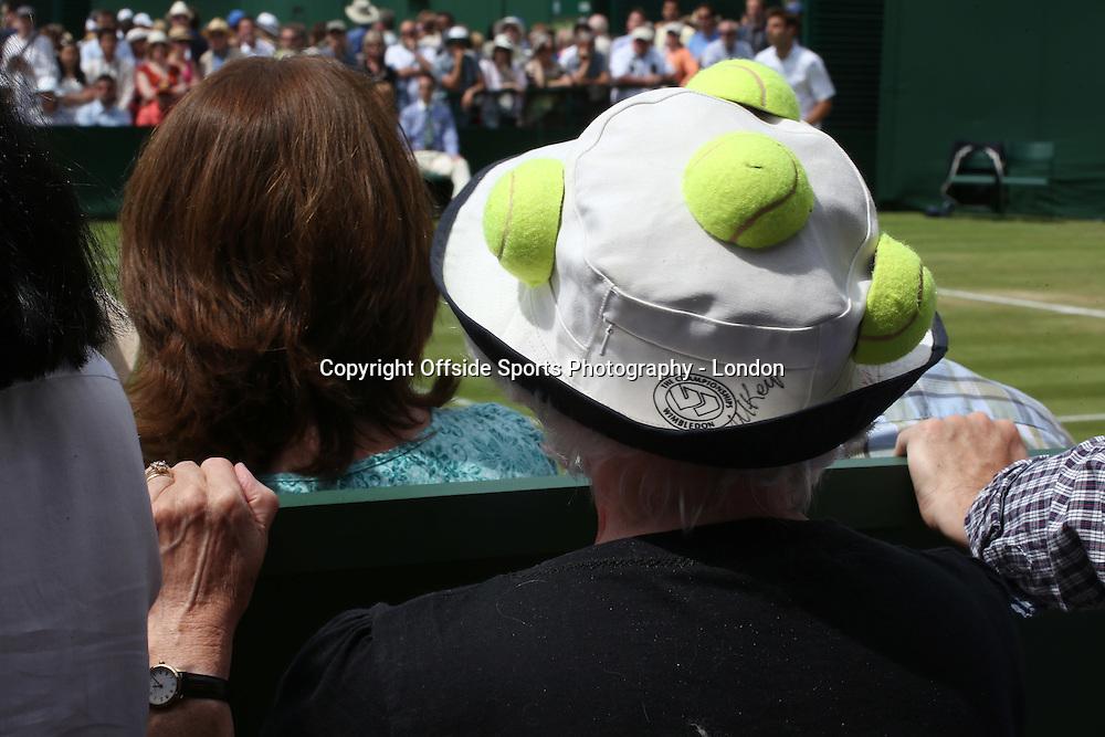 25 June 2014 Wimbledon Tennis - a female spectator wearing a tennis ball hat.