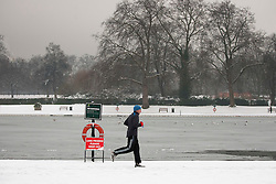 © Licensed to London News Pictures. 05/02/2012. LONDON, UK. A jogger runs on the snowy banks of a frozen Serpentine Lake in Hyde Park, London today (05/02/12). Millions of Britons woke up to a snowy Sunday after heavy snow fall covered much of the UK. Photo credit: Matt Cetti-Roberts/LNP