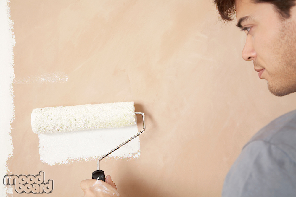 Man painting wall with paint roller indoors close up