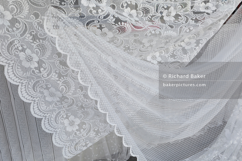 A detail of net curtains in the window of a home furnishings business, on 31st March 2019, in Faversham, Kent, England.