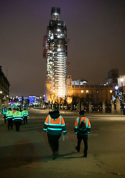 © Licensed to London News Pictures. 31/12/2018. London, UK. Event security personnel pass through an empty Parliament Square before the crowds arrive to celebrate New Year's Eve in central London.  Over 100,000 people are attending London's ticketed fireworks display on the banks of the River Thames for New Year's Eve tonight. Photo credit: Peter Macdiarmid/LNP
