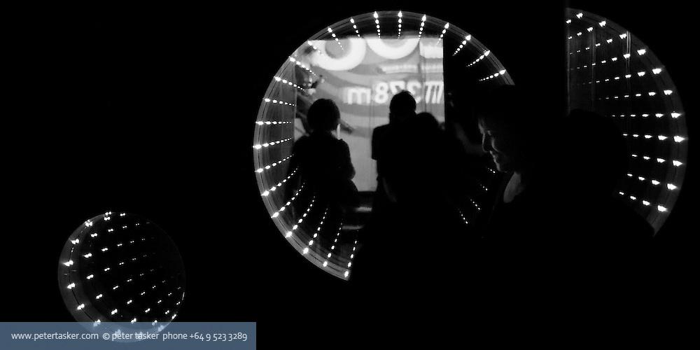 Tourist beside radial light display, inside Taipei 101.