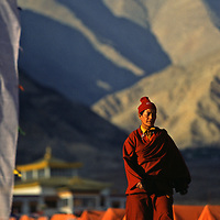 A buddhist monk walk in front of hundreds of tents display outside the Hemis Festival in honor of Guru Padma Sambhav´s birth anniversary. at the Hemis Monastery, 40 km from Leh, India,  It also has the largest Thangkha in  Ladakh, which is unfurled, once in 12 years. July 2004.