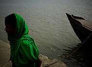 A girl and a boat on the bank of the Meghna river...This area in the south of Bangladesh has been called ground zero of climate-change due to heavy river and ocean erosion. The lowlying area is also hugely affected by cyclones and rising sea-levels...By the Mouth of Ganges, at the Bay of Bengal is the Island of Bhola. This home of about two million people is considered to be ground zero of climate change. Half the island has disappeared in the past 40 years, and according to scientists the pace is not going to slow down. People pack up and leave as the water get closer. Some to a nearby embankment, while those with enough money move further inland, but for most life move on until the inevitable. It's always about survival for the people in one of the worlds poorest countries...Photo by: Eivind H. Natvig/MOMENT