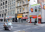 © licensed to London News Pictures. New York, USA  28/05/11. A man pushes a drinks cart past a McDonald's Restaurant, early morning on Broadway. Photo credit should read Stephen Simpson/LNP