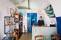 """PISCIOTTA, ITALY - 22 APRIL 2018: Marco Rimbaldo (26) is seen here at the counter of the """"Alici di Menaica"""" store owned by his parents Donatella Marina and Vittorio Rimbaldo in Pisciotta, Italy, on April 22nd 2018.<br /> <br /> Former restaurant owners Donatella Marino and her husband Vittorio Rimbaldo have spent the recent years preparing and selling salted anchovies, called alici di menaica, to a growing market thanks to a boost in visibility from the non-profit Slow Food.  The ancient Menaica technique is named after the nets they use brought by the Greeks wherever they settled in the Mediterranean. Their process epitomizes the concept of slow food, and involves a nightly excursion with the special, loose nets that are built to catch only the larger swimmers. The fresh, red anchovies are immediately cleaned and brined seaside, then placed in terracotta pots in between layers of salt, to rest for three months before they're aged to perfection.While modern law requires them to use PVC containers for preserving, the government recently granted them permission to use up to 10 chestnut wood barrels for salting in the traditional manner. The barrels are """"washed"""" in the sea for 2-3 days before they're packed with anchovies and sea salt and set aside to cure for 90 days. The alici are then sold in round terracotta containers, evoking the traditional vessels that families once used to preserve their personal supply.<br /> <br /> Unlike conventional nets with holes of about one centimeter, the menaica, with holes of about one and half centimeters, lets smaller anchovies easily swim through. The point may be to concentrate on bigger specimens, but the net also prevents overfishing."""