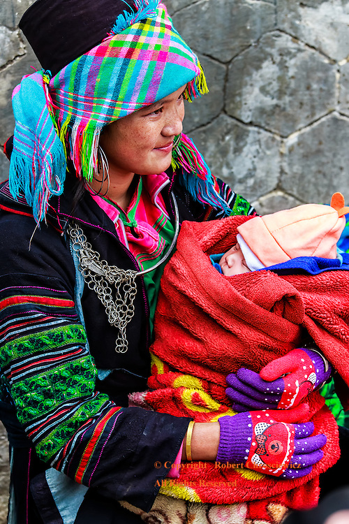 Hmong Mother and Child: A young mother, of a local Hmong hill tribe, wearing a mixture of modern and traditional clothing, proudly holds her new born child, Sapa Vietnam.