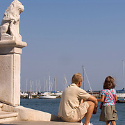 Father and daughter at foot of Vigo Bridge watching boats in the lagoon at Chioggia Italy