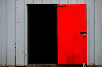 A red door opens to blackness of a warehouse.