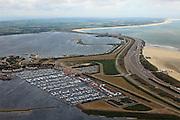 Nederland, Zuid-Holland, Ouddorp  22-05-2011; Brouwersdam, onderdeel van de Deltawerken, tussen Goeree en Schouwen met links het Grevelingenmeer de Middelplaat met recreatiecentrum en vakantiepark Port Zelande. Na het afsluiten van de zeearm Grevelingen zijn gaandeweg ernstige milieuproblemen ontstaan in het zoetwatermeer met name algengroei. Er zijn plannen om een opening in de dam te maken om zo het getij deels terug te laten keren..Brouwersdam, part of the Delta Works, between Goeree and Schouwen. Left Grevelingenmeer and Middelplaat with the recreation and park Port Zelande. The closure of the ester lead to increasing serious environmental problems in freshwater lake in particular algae. There are plans for an opening in the dam  allowing the tidiest return partially..luchtfoto (toeslag); aerial photo (additional fee required);.foto Siebe Swart / photo Siebe Swart