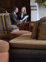 Business man and woman talking in lobby sofas in foreground