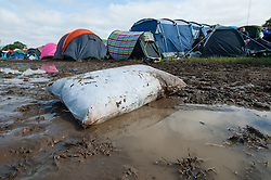 © Licensed to London News Pictures. 13/06/2015. Isle of Wight, UK.  A lone pillow lies in the campsite mud at Isle of Wight Festival 2015 on the morning of Saturday Day 3.  Yesterday suffered torrential rain all afternoon and evening, after a first day of warm sun.  This years festival include headline artists the Prodigy, Blur and Fleetwood Mac.  Photo credit : Richard Isaac/LNP