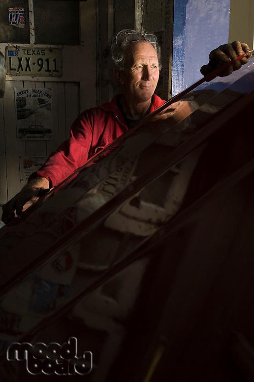 Senior Man in Garage with Vintage Car