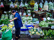 "04 DECEMBER 2018 - BANGKOK, THAILAND:  A shopper in Khlong Toei market surrounded by produce in single use plastic bags. The issue of plastic waste became a public one in early June when a whale in Thai waters died after ingesting 18 pounds of plastic. In a recent report, Ocean Conservancy claimed that Thailand, China, Indonesia, the Philippines, and Vietnam were responsible for as much as 60 percent of the plastic waste in the world's oceans. Khlong Toey (also called Khlong Toei) Market is one of the largest ""wet markets"" in Thailand. December 4 was supposed to be a plastic free day in Bangkok but many market venders continued to use plastic.     PHOTO BY JACK KURTZ"