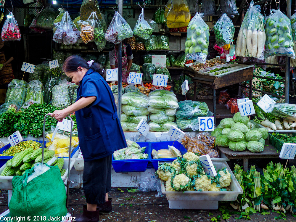 """04 DECEMBER 2018 - BANGKOK, THAILAND:  A shopper in Khlong Toei market surrounded by produce in single use plastic bags. The issue of plastic waste became a public one in early June when a whale in Thai waters died after ingesting 18 pounds of plastic. In a recent report, Ocean Conservancy claimed that Thailand, China, Indonesia, the Philippines, and Vietnam were responsible for as much as 60 percent of the plastic waste in the world's oceans. Khlong Toey (also called Khlong Toei) Market is one of the largest """"wet markets"""" in Thailand. December 4 was supposed to be a plastic free day in Bangkok but many market venders continued to use plastic.     PHOTO BY JACK KURTZ"""