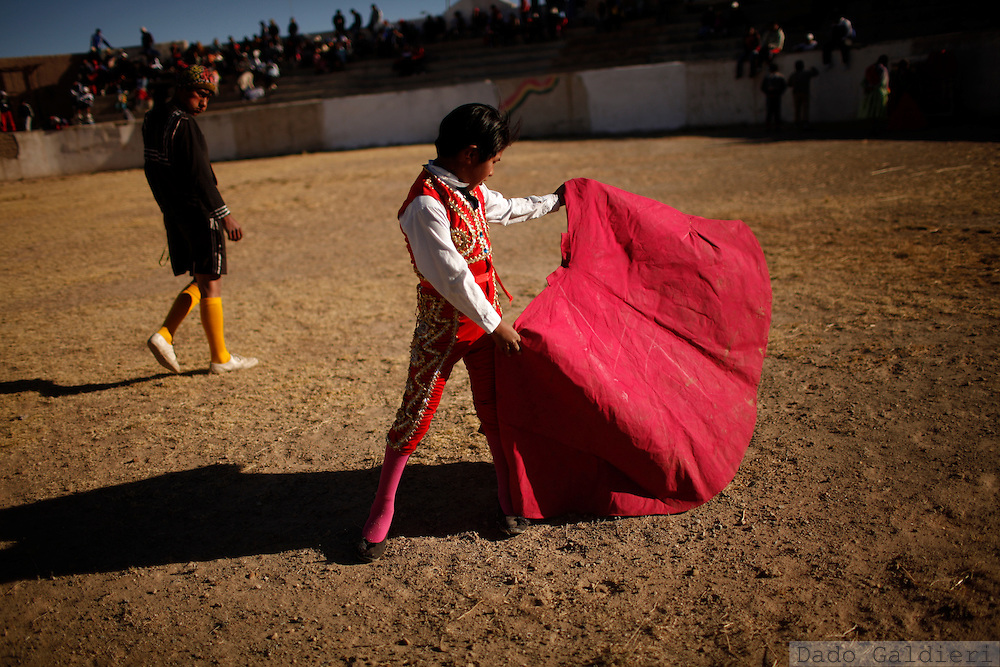 Mauricio Copa, 11, tries some movements dressing a bullfighter's costume before performing in a bullfight parody in the Andean village of Vinto, Bolivia, Saturday July 10, 2010. A group of traveling amateur bullfighters presented a parody of the Spanish bullfight, but without the traditional sacrificing of the bull, as part of their tour through Bolivia's highlands providing entertainment during the southern hemisphere winter.