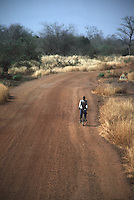 A young man rides his bicycle along a dirt road in rural Mali.