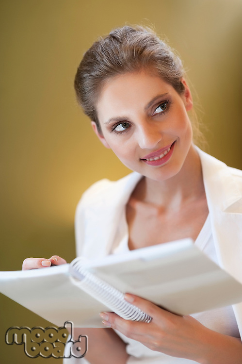 Young woman looking sideways while writing notes on spiral notebook