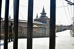 March 22, 2019 - Srinagar, J&K, India - A paramilitary trooper seen standing  alert outside the historic Grand Mosque Jamia Masjid during the restrictions in Srinagar, Kashmir..Authorities imposed restrictions in Old City of Srinagar following the protest call given by the separatist leaders against the custodial killing of Rizwan Pandit who died in a police custody after he was arrested in connection with a terror case investigation. (Credit Image: © Saqib Majeed/SOPA Images via ZUMA Wire)