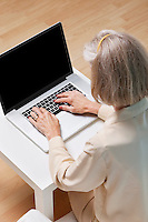 Senior woman surfing the net on laptop at home