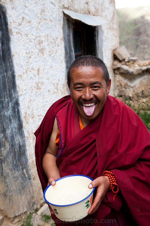 The head monk extends his tongue to greet visitors at the reconstructed monastery in the Tibetan Plateau. (From the book What I Eat; Around the World in 80  Diets.) An extended tongue is a common greeting that indicates respect. MODEL RELEASED.