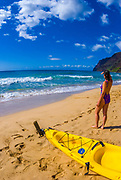 Woman and sea kayak at Polihale Beach, Polihale State Park, Island of Kauai, Hawaii USA