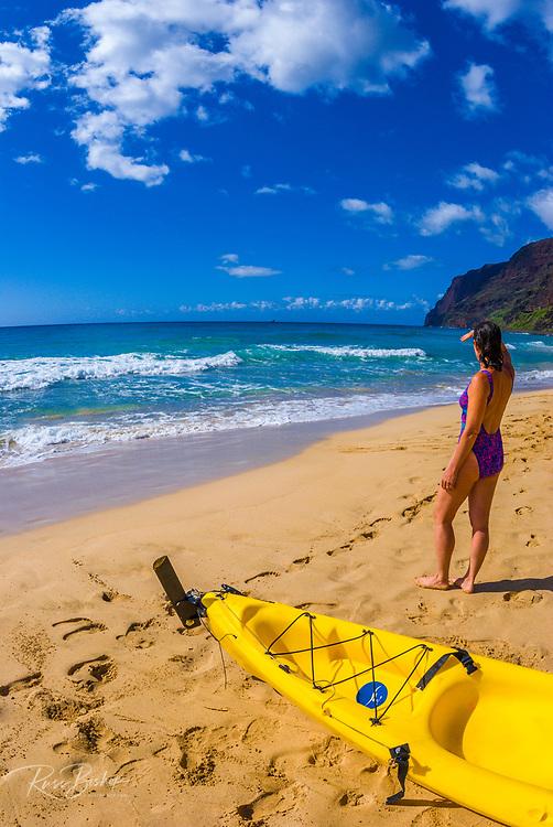Woman and sea kayak at Polihale Beach, Polihale State Park, Island of Kauai, Hawaii USA